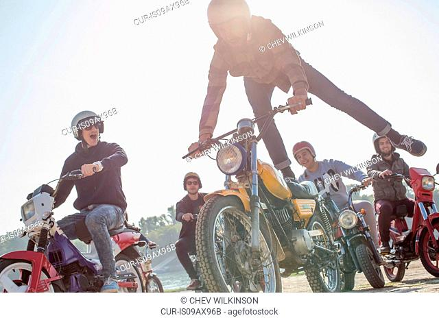 Group of friends riding mopeds along road, man in mid air, doing stunt