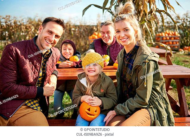 Portrait of three generation family at pumpkin patch picnic table