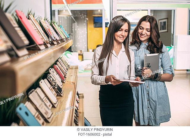 Young saleswoman showing brochure to female customer at electronics store