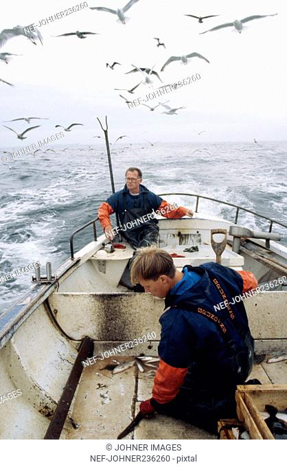 Two fishermen working on a boat