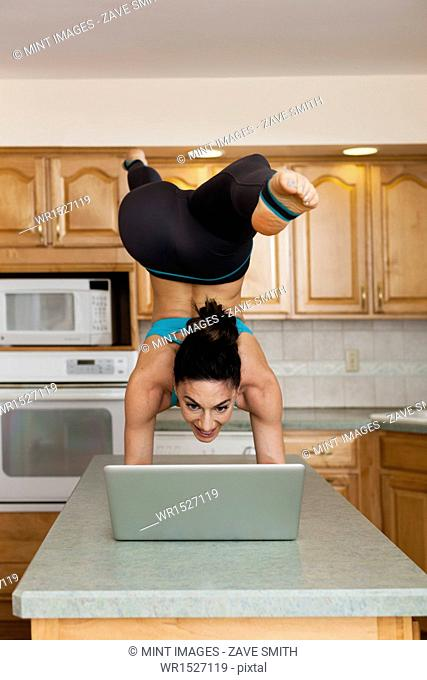 A woman doing a handstand balancing on a kitchen top and checking her laptop