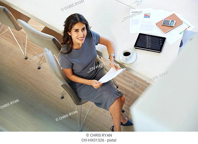 Portrait smiling businesswoman reviewing paperwork and drinking coffee at conference table