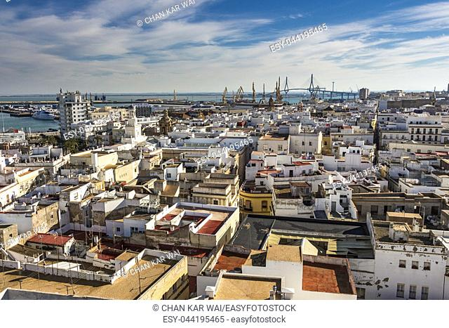 Aerial east view of buildings near Port of the Bay of Cadiz. In the far distance is the Constitution of 1812 Bridge