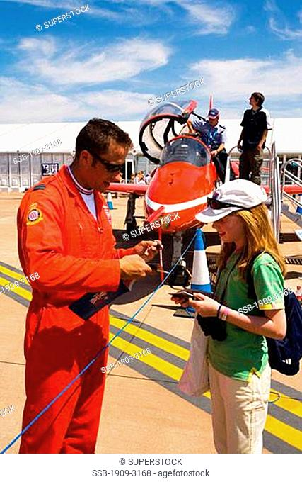 Red Arrows RAF aerobatic display team pilot signs autograph for lucky young girl at Fairford International Air Show 2006 Gloucestershire England Great Britain...