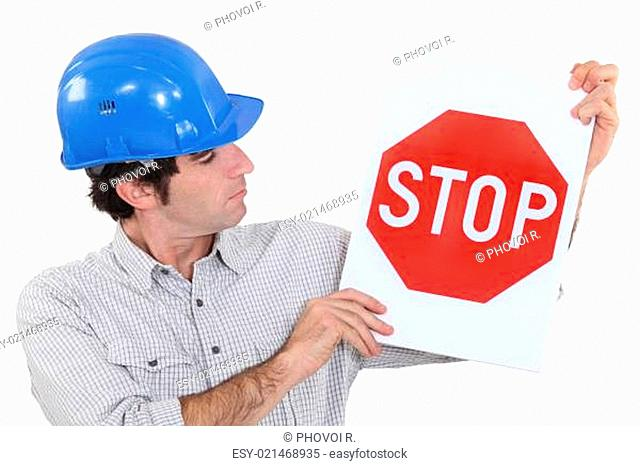 man wearing a helmet and holding a stop sign