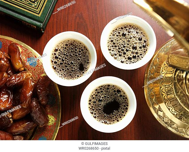 Cups of coffee and plate of dates