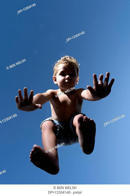 Low angle view of a child in mid-air against a blue sky; Tarifa, Cadiz, Andalusia, Spain
