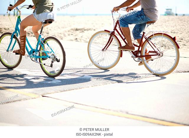Neck down view of couple cycling at Venice Beach, Los Angeles, California, USA