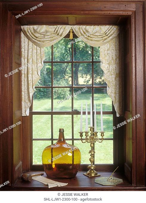 WINDOW TREATMENTS: Daniel Boone home. Handblown colored glass jug and brass candelabra sit in window sill, double hung window, floral pattern swag and jabots