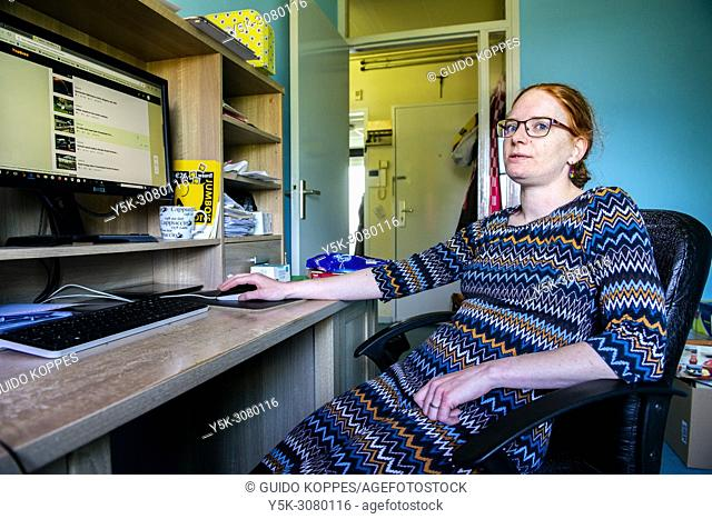 Roosendaal, Netherlands. Young woman working at home, using her computer, where she upload smartphone made movies to a video website for others to view and...