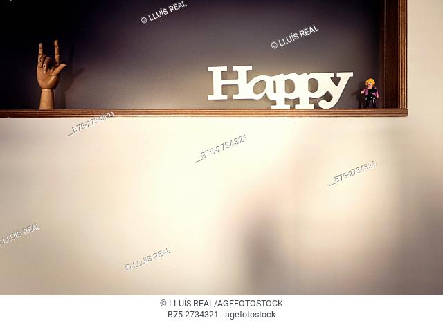 """Shelf with wooden hand, toy figure and """"Happy"""" text"""