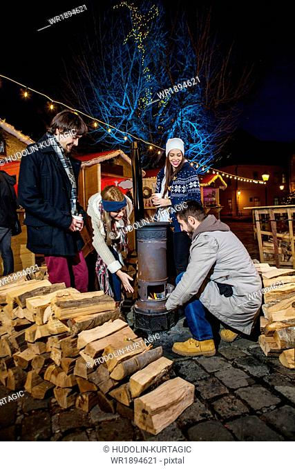Four friends warming up by stove at Christmas Market