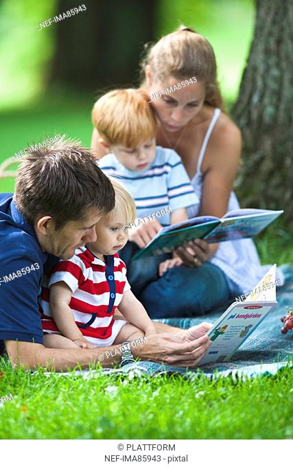 Mid adult parents reading books to children during picnic