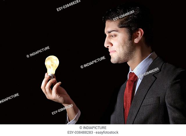 Businessman looking at light bulb