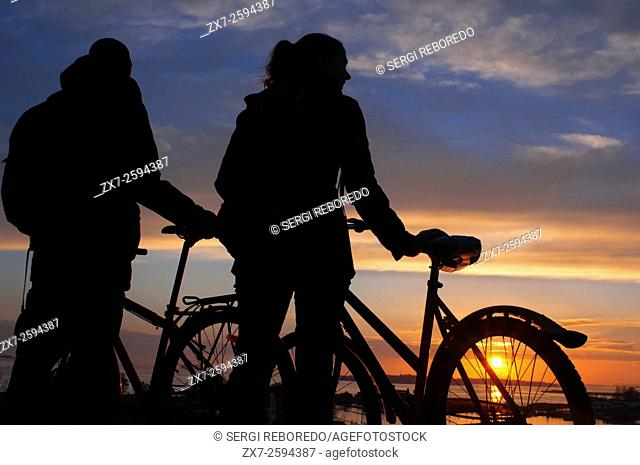 Bikers in Kaivopuisto park at sunset, Helsinki, Finland. The sunsets from the southern part of Helsinki in Kaivopuisto not leave anyone indifferent