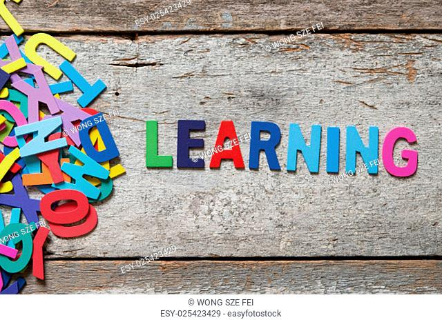 """The colorful words """"""""LEARNING"""""""" made with wooden letters next to a pile of other letters over old wooden board"""