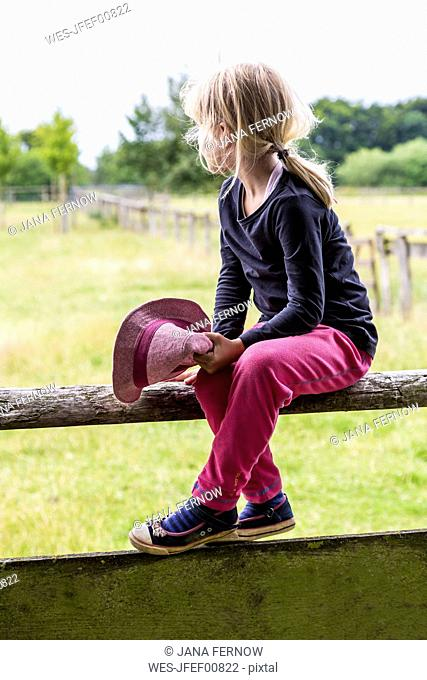 Blond little girl sitting on bar looking at distance