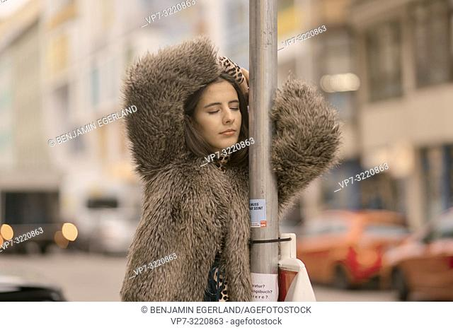 young woman with closed eyes leaning on traffic sign at street in city, relaxed mood, in Munich, Germany