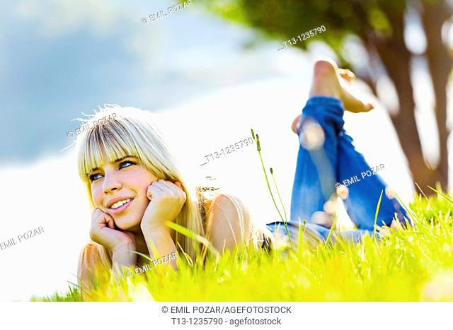 Enjoying sun teen girl is lying on the grass