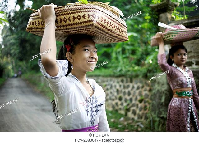 Two girls with offerings on their way to the temple during Kuningan Festival; Bali, Indonesia