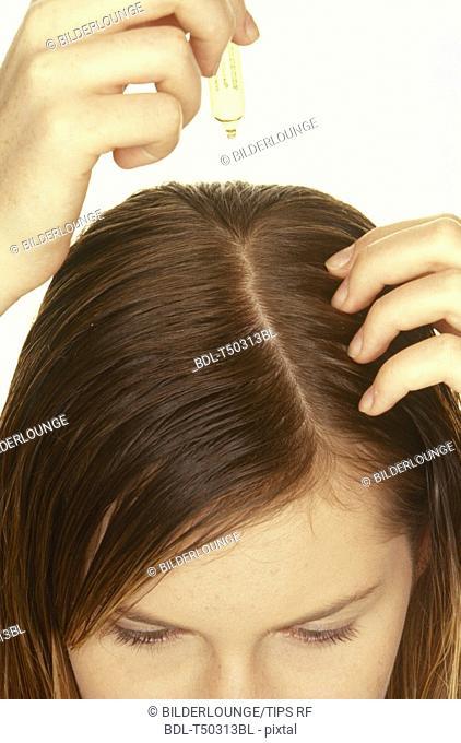 Woman applying hair treatment