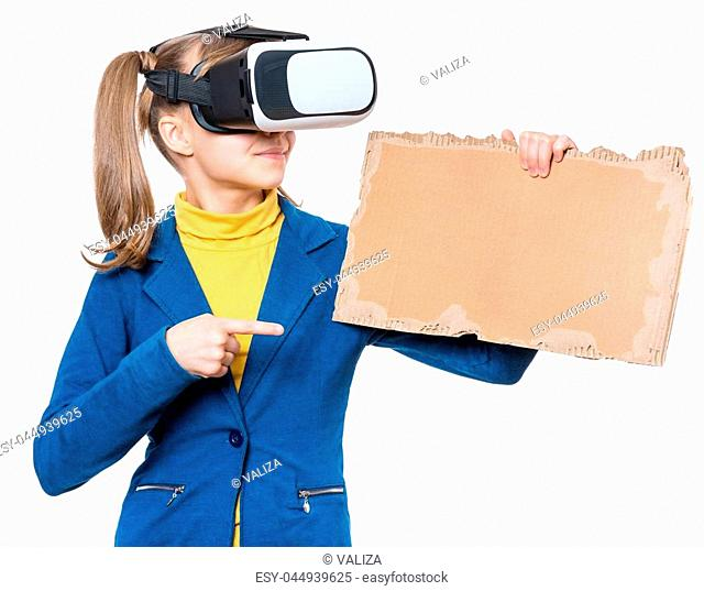 Happy little girl wearing virtual reality goggles watching movies or playing video games. Kid with VR glasses and corrugated cardboard torn pieces