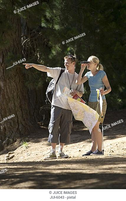 Couple hiking on woodland trail, man with map pointing, woman looking through binoculars, smiling