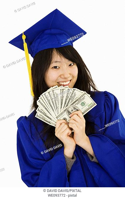 An Asian teenage in blue graduation gown and smiling while hold US money to illustrate to high cost of education  She is on a white background