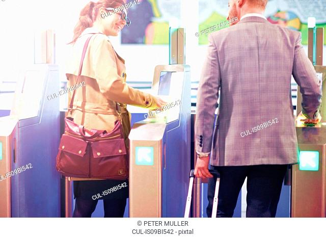 Businessman and woman walking through security gate at airport, rear view