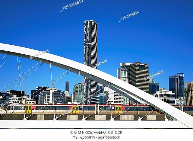 suburban train crossing railway bridge over Brisbane River, with city skyline, Australia