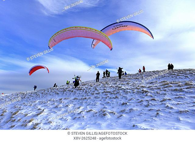 Paragliders about to take off from snowy Mam Tor near Castleton, Derbyshire, Peak District National Park, England, UK
