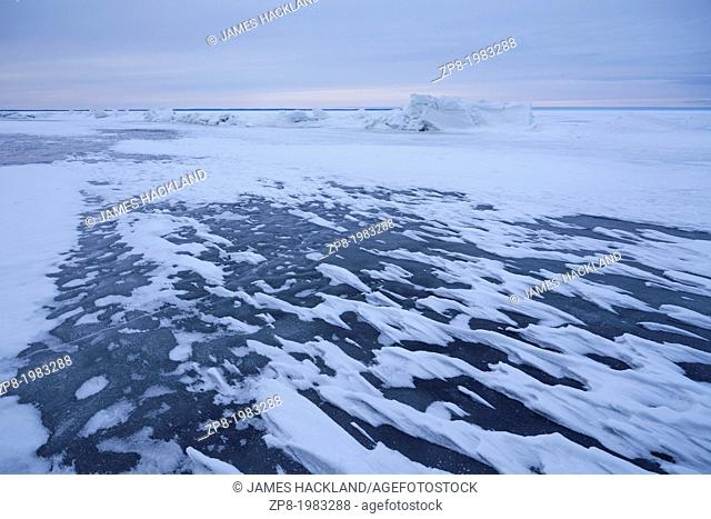 Frozen snow formations caused by intense wind on a frozen lake in Ontario, Canada