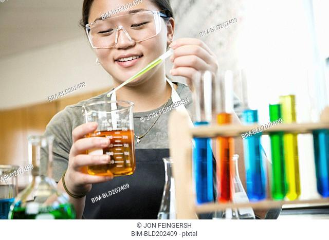 Asian student working with chemicals in classroom