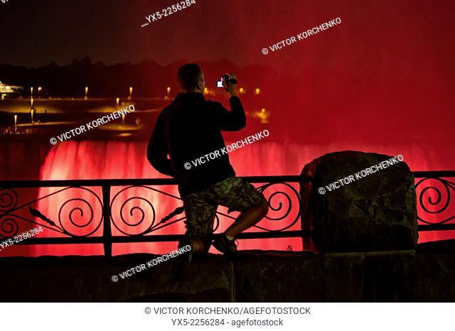 Man taking a video shot of Niagara Falls illuminated at night