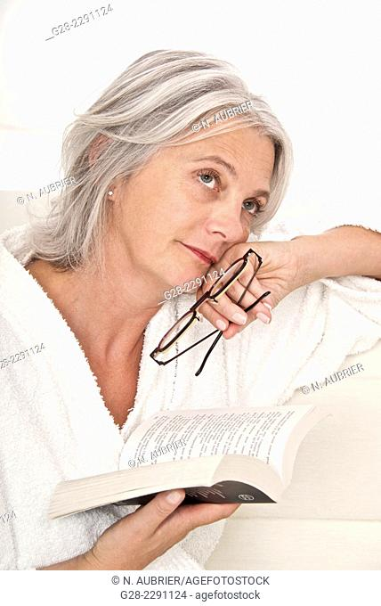 Beautiful senior woman sitting on a sofa and reading a book, holding a pair of glasses in her hand, and day dreaming