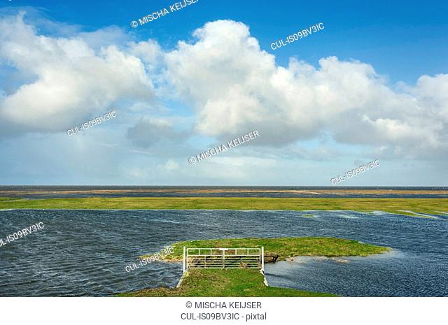 Field landscape with standing water due to high tide and strong winds, polders beyond sea dyke have flooded, Netherlands