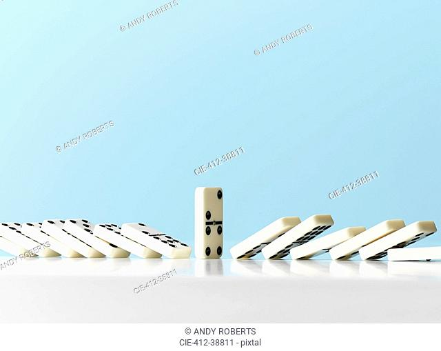 Dominos falling around standing domino against blue background