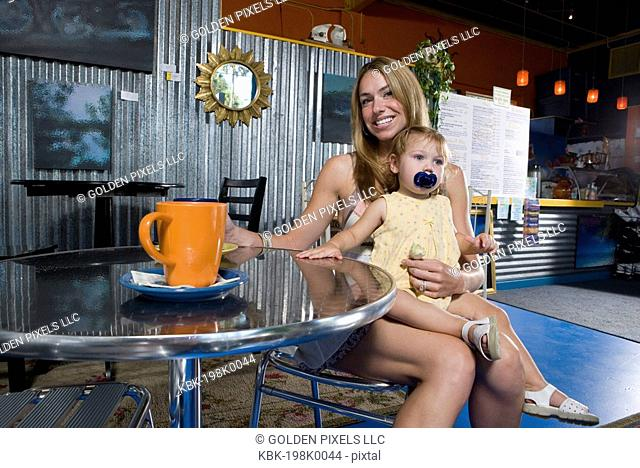 Young woman sitting in a cafi with her baby on her lap