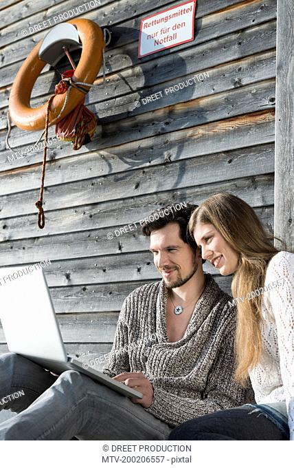 Portrait young couple using laptop outdoors