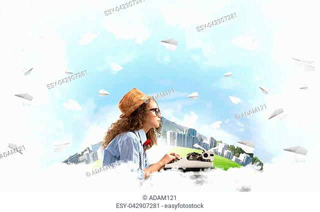 Young woman writer in hat and eyeglasses using typing machine while sitting at the table among flying paper planes with floating city island and cloudy skyscape...