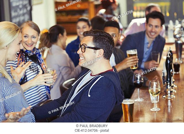 Enthusiastic man and woman greeting in bar