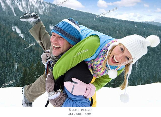 Man carrying girlfriend over shoulders through snow