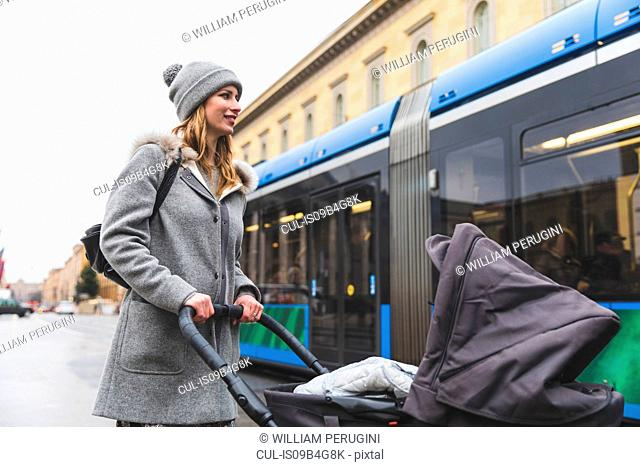 Mid adult woman getting on bus with baby carriage