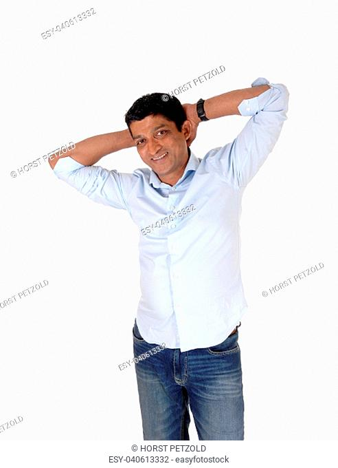 A happy smiling Asian man standing in jeans and a light blue shirt with.his hands behind his head, isolated for white background