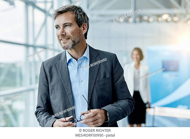 Smiling businessman and businesswoman at the airport