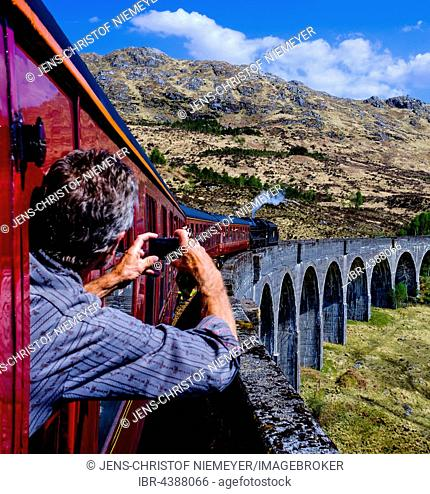 Man leans out the window taking a picture of historic train The Jacobite Steam Train driving over the Glenfinnan Viaduct, Glenfinnan, Highland, Scotland