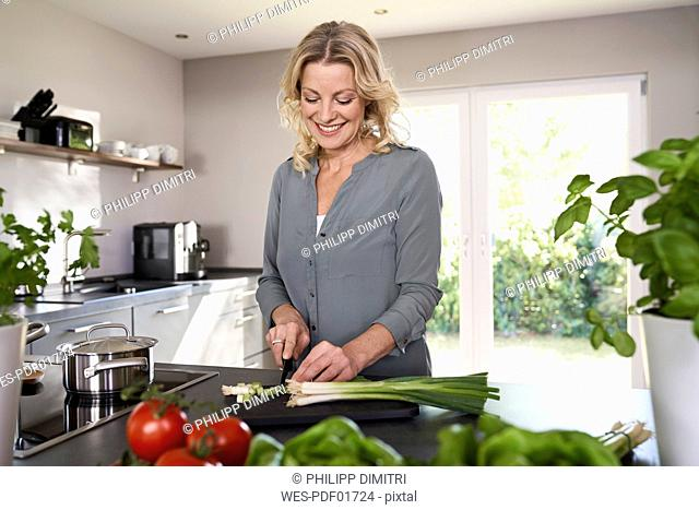 Smiling woman cutting spring onions in kitchen