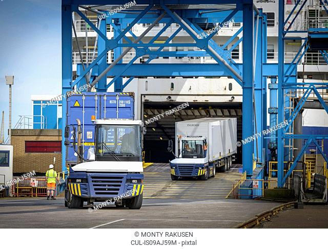 Truck loading containers onto ship in port