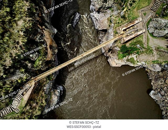 Peru, Quehue, aerial view of woman crossing rope bridge