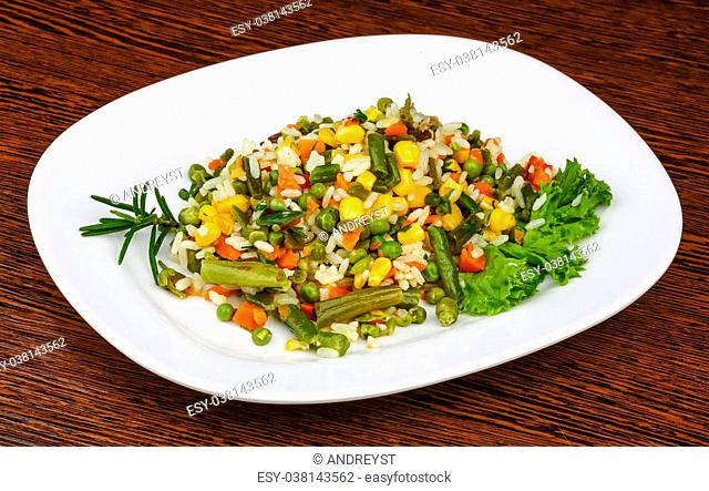 Mexican rice with vegetables and salad leaves